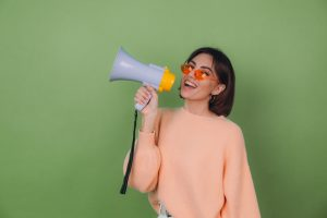 young-woman-casual-peach-orange-eyeglasses-sweater-isolated-green-olive-wall-happy-screaming-megaphone-copy-space